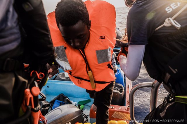HANDOUT - 04 July 2021, Italy, ---: A migrant is helped out of a small boat. The Ocean Viking rescue vessel has pulled 67 people from the central Mediterranean Sea, SOS Mediterranee the private organization that runs the vessel, said on Sunday. Photo: Fla