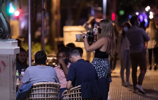Archivo - Una camarera atiende a varias personas en la terraza de un bar de copas.