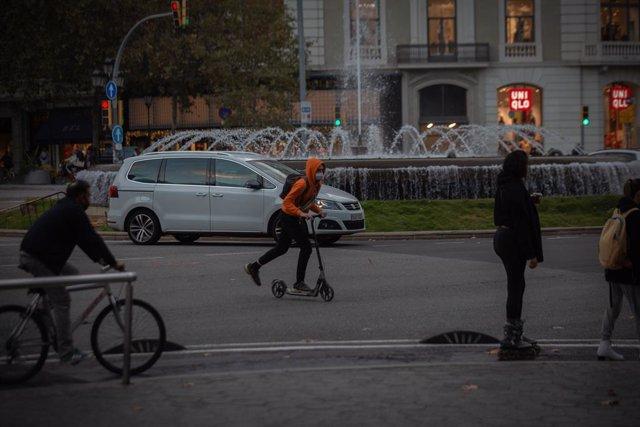 Archivo - Arxiu - Un home amb bici i un jove amb patinet a Barcelona