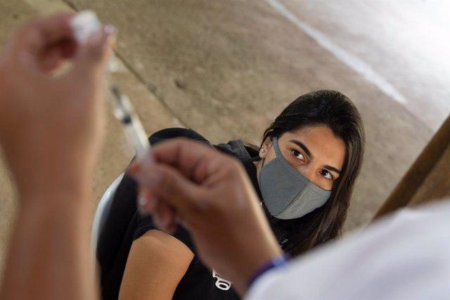 20 June 2021, Brazil, Rio de Janeiro: A medical assistant prepares to vaccinate a young woman (R) against Coronavirus (Covid-19) on the island of Ilha de Paqueta. Photo: Fernando Souza/dpa