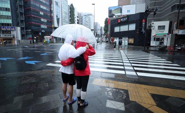 Archivo - Una pareja se cubre con un paraguas en una calle de Tokio.