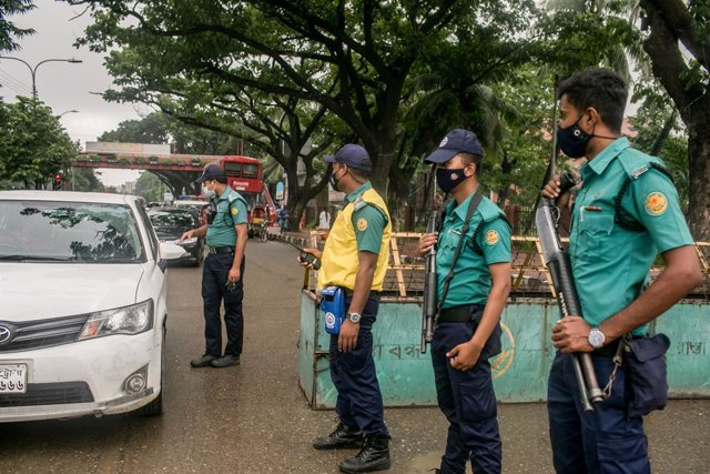 04 July 2021, Bangladesh, Dhaka: Police officers inspect a vehicle at a checkpoint in Dhaka during the covid-19 lockdown. Bangladesh is extending its current nationwide shutdown for seven more days with tighter restrictions to counter a rise in coronaviru