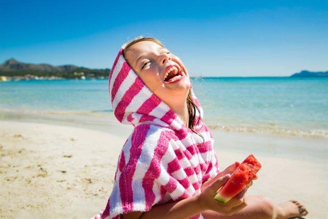 Archivo - Niña feliz, playa, verano, risa, sandía, dientes