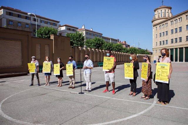 El consejero de Políticas Migratorias y Justicia, Eduardo Santos (centro) en la presentación de los carteles informativos sobre la vacuna contra el Covid-19 para la población migrante