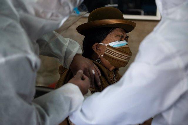 Archivo - 27 April 2021, Bolivia, La Paz: A woman with double oral-nasal protection Receives the Sputnik V Coronavirus vaccine in the library room of the Universidad de San Andres. Photo: Radoslaw Czajkowski/dpa