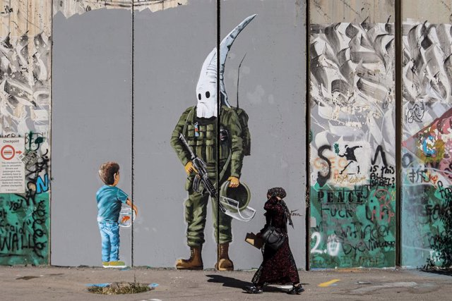 Archivo - 29 May 2021, Palestinian Territories, Bethlehem: A Palestinian woman walks past a graffiti mural depicting a boy holding a fishbowl looking at a uniformed Israeli soldier wearing a KKK-style hood, painted by Palestinian artist Taqi Spateen along
