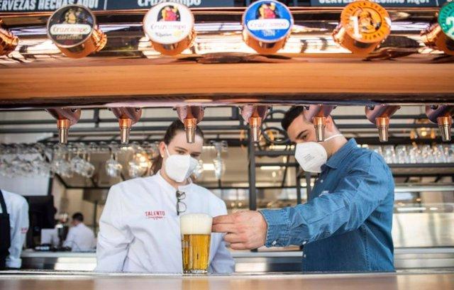 Dos camareros sirviendo una cerveza Cruzcampo en su establecimiento.