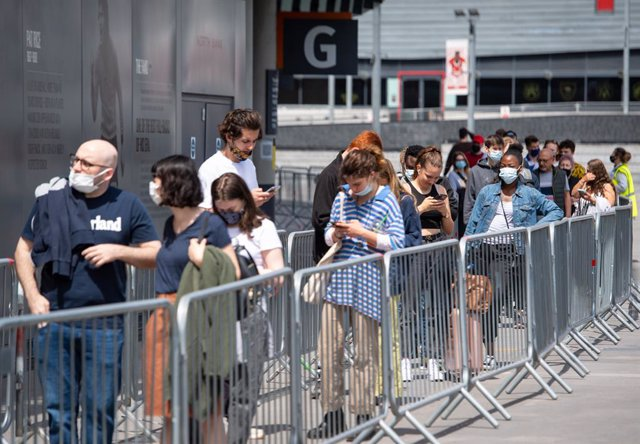 25 June 2021, United Kingdom, London: People queue outside a Covid-19 vaccination centre set up in the Emirates Stadium, the football stadium of the English premier league club Arsenal FC. Photo: Dominic Lipinski/PA Wire/dpa