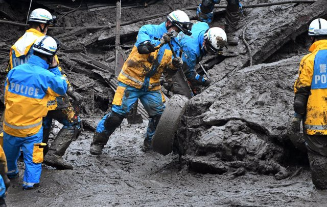 04 July 2021, Japan, Atami: Rescue workers take part in a searching operation for missing victims at the scene of a mudslide in the Japanese city of Atami. Rescuers were battling against time and the weather on Sunday in the search for about 20 people who
