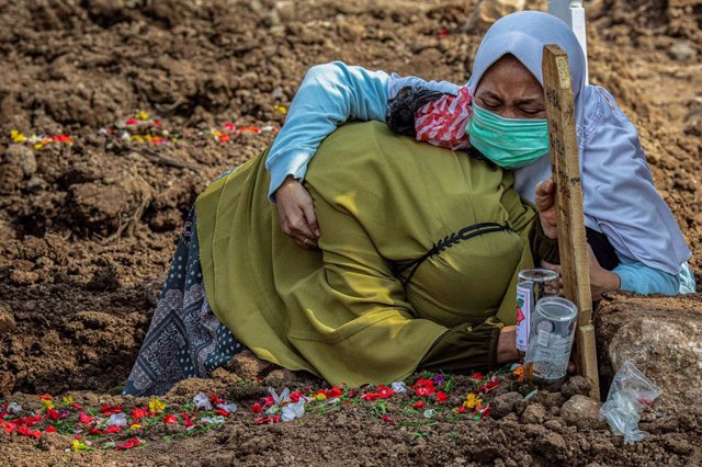 28 June 2021, Indonesia, Jakarta Utara: Two women grieve on the grave of a relative who died of coronavirus complications. Photo: Donal Husni/ZUMA Wire/dpa