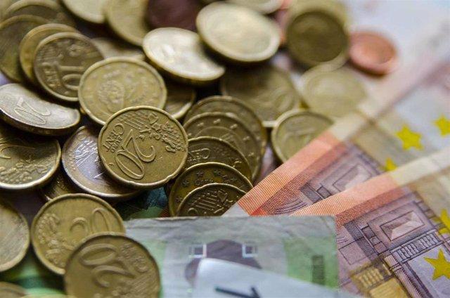 Archivo - Monedas y billetes en euros