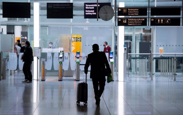 Archivo - 26 March 2021, Bavaria, Munich: A man goes to the security check with his suitcase at Munich airport. A new requirement for people arriving at German airports to have submitted to coronavirus testing has been postponed from Sunday to Tuesday. Ph