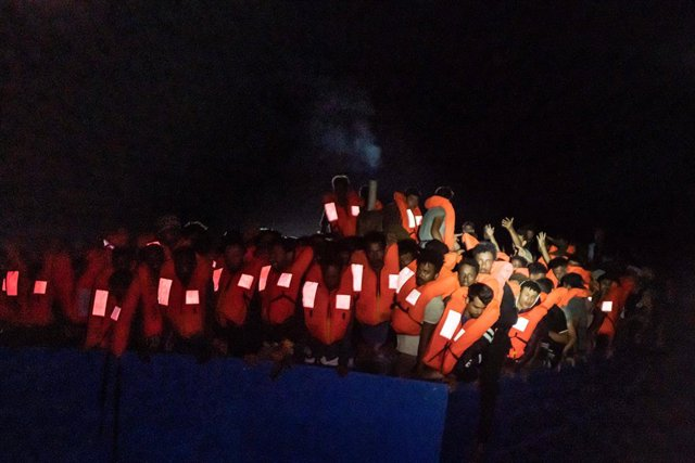 HANDOUT - 05 July 2021, ---, Mediterranean Sea: Numerous refugees are crowded together on a boat at night. The private sea rescuers of the ship Ocean Viking have rescued several hundred boat migrants in the central Mediterranean Sea in a major operation.