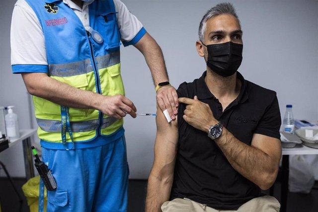 Un sanitario administra una dosis de la vacuna de Pfizer a un hombre en el Wizink Center