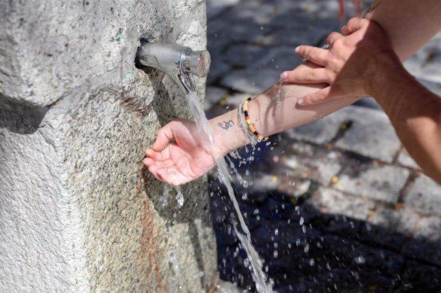 Archivo - Un joven se moja las manos y brazos en una fuente.