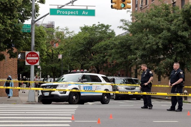 12 June 2021, US, New York City: Police officers investigate the scene at Prospect Avenue in the Longwood-section of the borough, where a person was shot by a gunman in front of St. Anthony of Padua Church. Photo: G. Ronald Lopez/ZUMA Wire/dpa