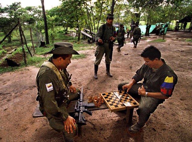 Archivo - Un grupo de guerrilleros de las ya disueltas FARC juega al ajedrez en una foto tomada en 2001 en un lugar indeterminado de Colombia.