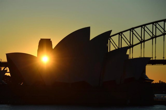 The sun is seen setting through the Sydney Harbour Bridge pylon lookout and through the sails of the Sydney Opera House in Sydney, Monday, July 5, 2021. (AAP Image/Mick Tsikas) NO ARCHIVING