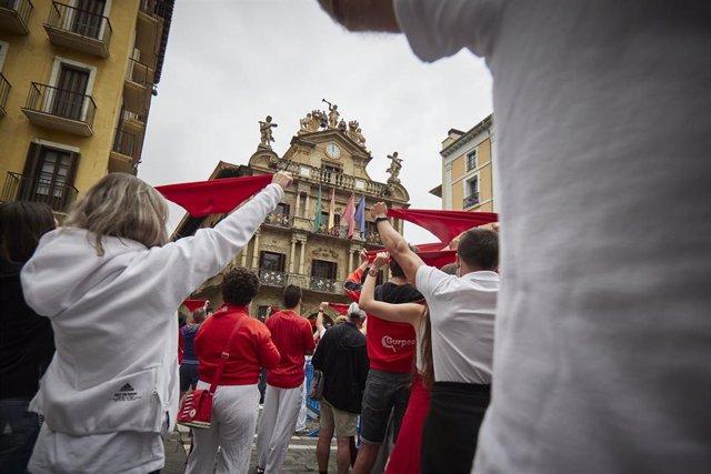 Un grupo de personas se concentra con pañuelos rojos al mediodía del 6 de julio de 2021, fecha en que habrían comenzado las fiestas de San Fermín, suspendidas por segundo año por la pandemia