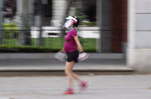 Archivo - Una mujer embarazada y con visera de protección pasea durante el tercer día de la desescalada del Gobierno en la fase 0 y el inicio de la semana octava del estado de alarma decretada por la crisis del coronavirus, en Madrid (España), a 4 de mayo