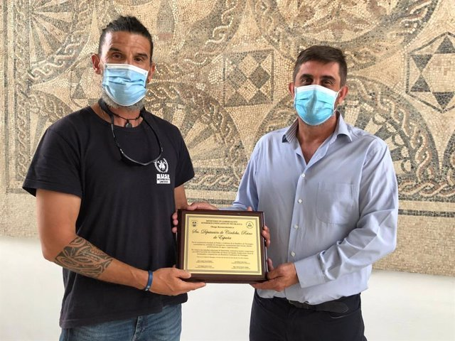El delegado de Cooperación al Desarrollo de la Diputación de Córdoba, Ramón Hernández (dcha.), recibe la placa de reconocimiento de manos de Antonio García, en representación de Bomberos Unidos Sin Fronteras.