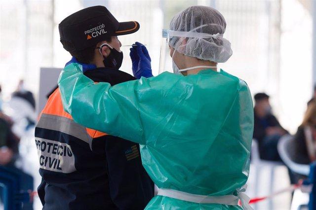 Archivo - Una trabajadora sanitaria protegida realiza un test de antígenos en el Polideportivo de ses Païsses, Sant Antoni, Ibiza.