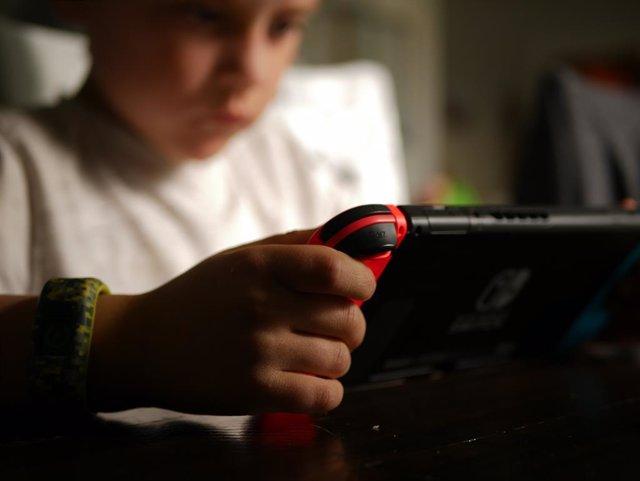 Niño jugando a videojuegos en una consola.