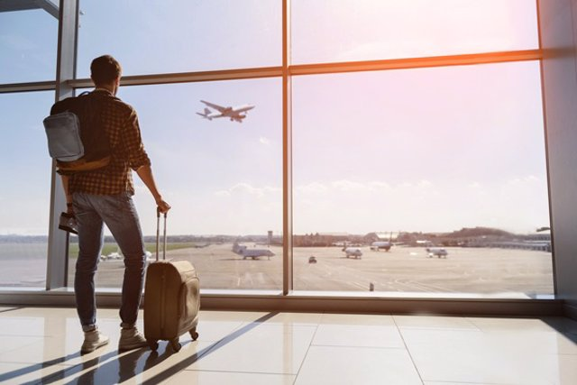 Archivo - Viajero en ventana de aeropuerto viendo despegar un avión.