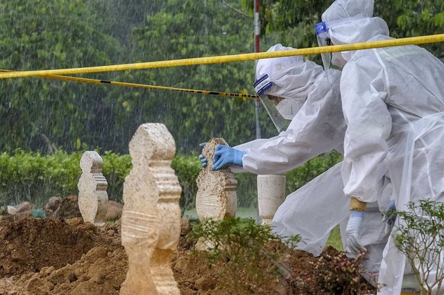 Trabajadores malayos poniendo tumbas en un cementerio a víctimas del coronavirus.
