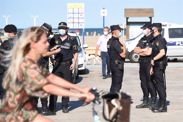 Varios agentes de Policía Local, preparan el desalojo de la playa de la Malvarrosa por la festividad de San Juan en València