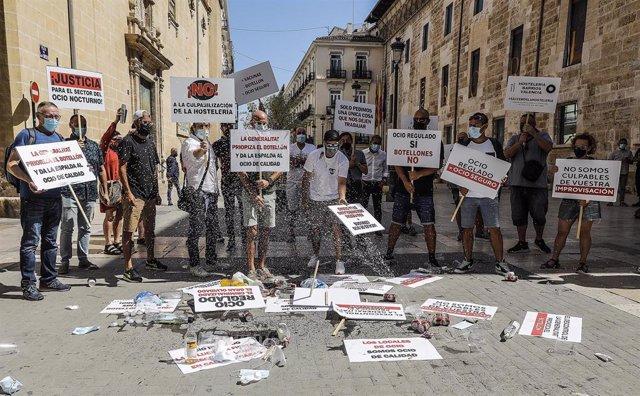 Varios trabajadores de pymes del ocio y de la hostelería con carteles, escenifican un 'botellón' para reclamar medidas efectivas que frenen los contagios y amparo económico, ante Les Corts