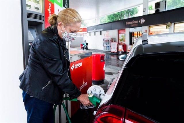 Una mujer pone gasolina a su vehículo en una gasolinera, a 17 de junio, en Madrid, (España). El coste medio del litro de gasolina ha registrado su tercera alza consecutiva para alcanzar los 1,367 euros, su nivel más alto desde hace casi siete años. Antes