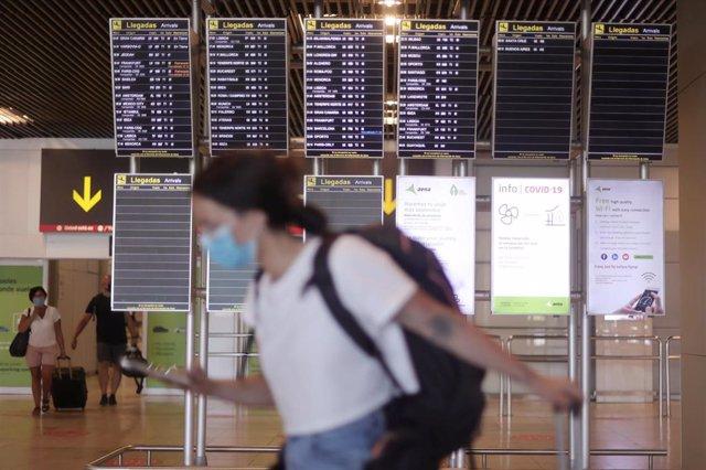 Una mujer camina con su equipaje en la terminal T1 del Aeropuerto de Madrid - Barajas Adolfo Suárez.