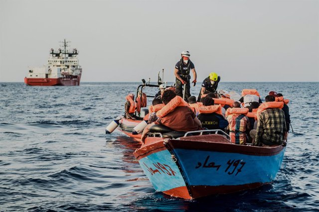 HANDOUT - 04 July 2021, Italy, ---: The helpers approach a small boat with migrants in their rubber dinghy in the Mediterranean Sea. The Ocean Viking rescue vessel has pulled 67 people from the central Mediterranean Sea, SOS Mediterranee the private organ