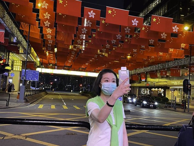 29 June 2021, China, Hong Kong: A woman takes a selfie near  China's national flags and the flags of the Hong Kong Special Administrative Region to mark the 24th anniversary of Hong Kong's handover to China. Photo: Dominic Chiu/SOPA Images via ZUMA Wire/d