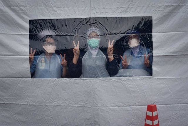 06 July 2021, Malaysia, Labuan: Health workers pose for a picture as they stand inside the vaccine preparation tent to work on the National COVID-19 Immunization Program (PICK) at the Universiti Malaysia Sabah Labuan International Campus (UMSKAL). Photo: