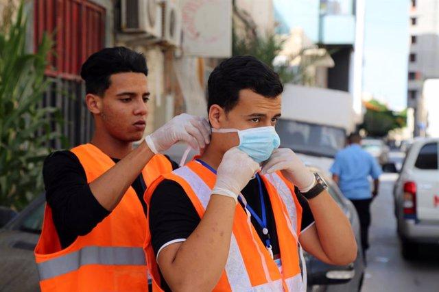 Archivo - Un grupo de jóvenes voluntarios durante las labores de desinfección de un hotel de Tripoli, Libia, en el marco de la crisis de la pandemia del nuevo coronavirus