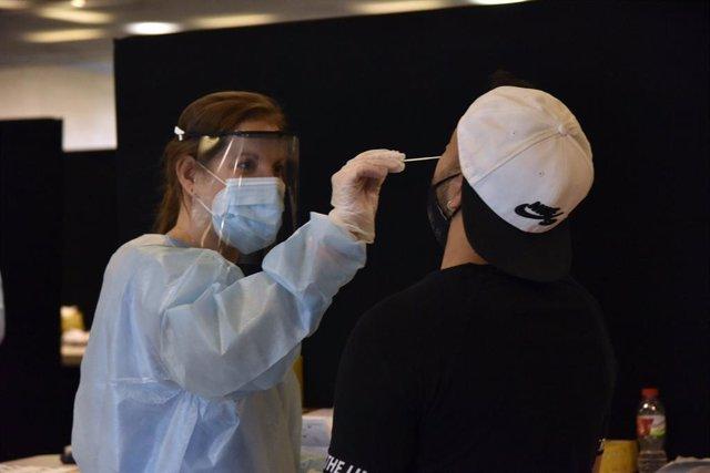 Arxiu - Una treballadora sanitària fa un test d'antígens a un jove