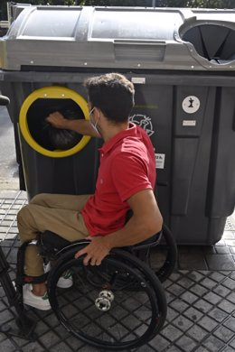 Un hombre en silla de ruedas usa el nuevo tipo de contenedor adaptado.