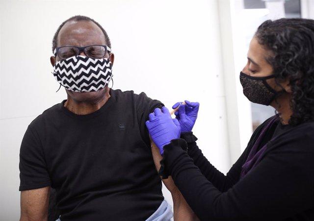Archivo - 09 April 2021, United Kingdom, London: Pharmacist Asha Fowells (R) vaccinates Paul Jinadu,79, with his second dose of the Oxford/AstraZeneca coronavirus vaccine, at Copes Pharmacy and Travel Clinic in Streatham, south London. Photo: Yui Mok/PA W