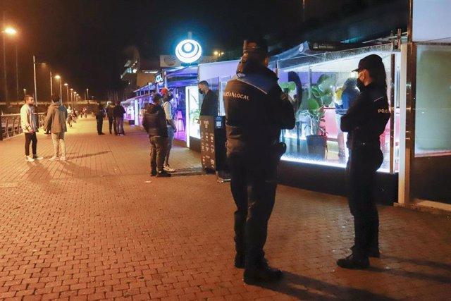Dos agentes de Policía Local pasean por el Puerto de Sanxenxo para informar en cada uno de los locales de ocio nocturno sobre las nuevas medidas Covid, en Sanxenxo, a 3 de julio de 2021, en Pontevedra, Galicia (España). Las autoridades pueden llegar a mul