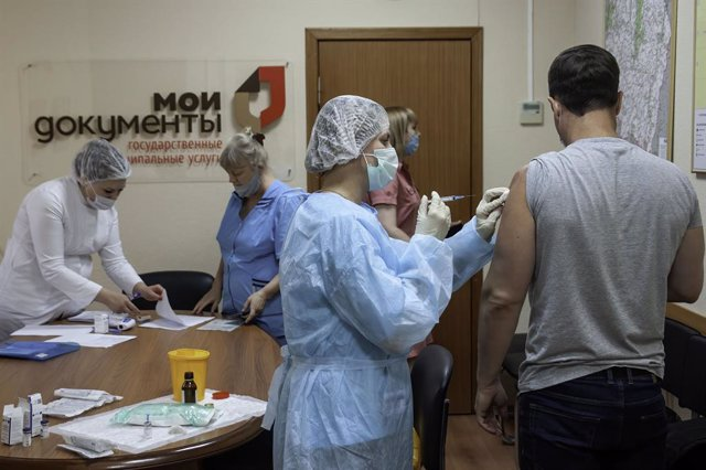 06 July 2021, Russia, Tambov: A nurse vaccinates an employee of the Multifunctional Center for the Provision of State and Municipal Services (the My Documents Center) with the Russian Gam-COVID-Vak coronavirus vaccine as many regions of Russia mandatory v