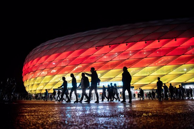 23 June 2021, Bavaria, Munich: Fans leave the Allianz Arena stadium, which is illuminated in the national colours of Germany, after the UEFA EURO 2020 Group F soccer match between Germany and Hungary. Photo: Matthias Balk/dpa