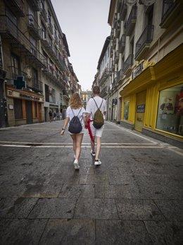 Dos jóvenes pasean por las calles de Pamplona durante el arranque de los 'No Sanfermines', a 6 de julio de 2021, en Pamplona, Navarra, (España). A pesar de que la ciudad de Pamplona se ha quedado por segundo año consecutivo sin Sanfermines debido a la pan