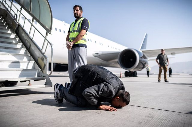 Archivo - 31 July 2019, Afghanistan, Kabul: An Afghan asylum seeker kisses the ground at the airport after leaving a charter plane. 45 rejected asylum seekers were deported form Germany on a special flight to Kabul. Photo: Michael Kappeler/dpa
