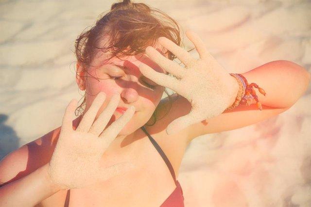 Archivo - Mujer protegiéndose del sol en la playa.
