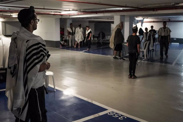 25 June 2021, Israel, Jerusalem: Jewish men, covered in prayer shawls, conduct their morning prayers in an underground parking lot while maintaining the social distancing. Israel reintroduced the mandatory wearing of face masks indoors on Friday in a bid