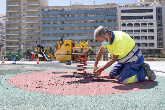 Operarios municipales reparan el suelo de caucho de un parque infantil