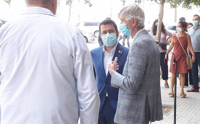El presidente de la Generalitat, Pere Aragonès, conversa con el conseller de Salud, Josep Maria Argimon, y sanitarios del Hospital de Bellvitge tras la rueda de prensa.