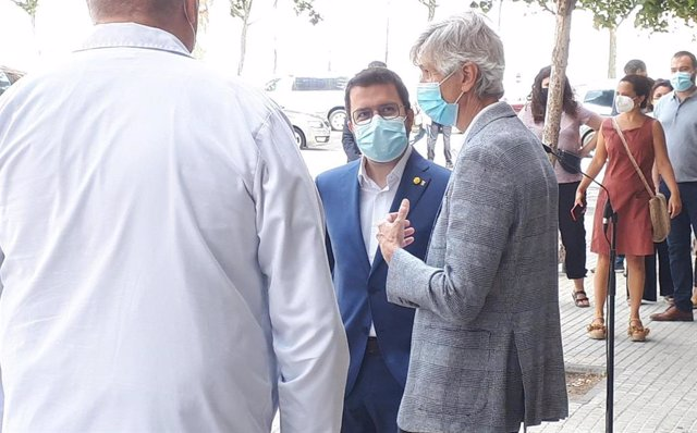 El president de la Generalitat, Pere Aragonès, conversa amb el conseller de Salut, Josep Maria Argimon, i sanitaris de l'Hospital de Bellvitge després de la roda de premsa.